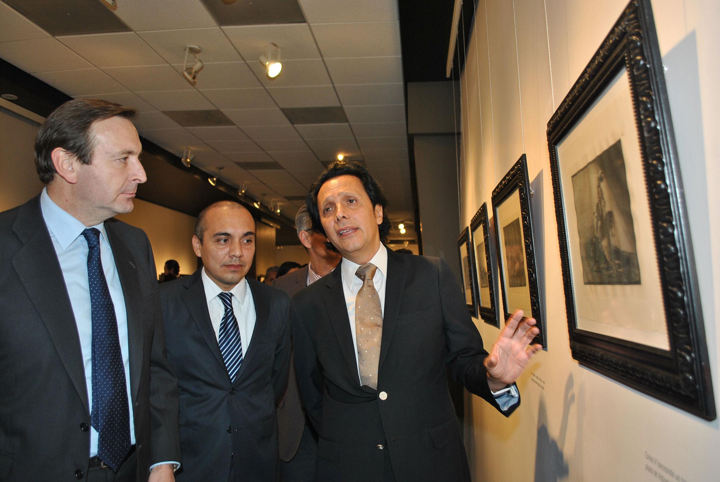 Luis Fernández-Cid de las Alas Pumariño, embajador de España (izquierda), observa la exposición mientras que Sergio Corella (derecha), le da la explicación de la obra